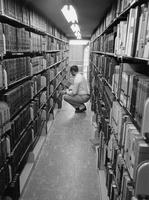 A student searches for books in the Stetson Library stacks