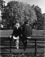 A female and male student sit on the Science Quad fence, 1969