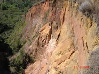 Steep exposures of laterite and saprolite, with some debris cones at base, in lavaka sidewall